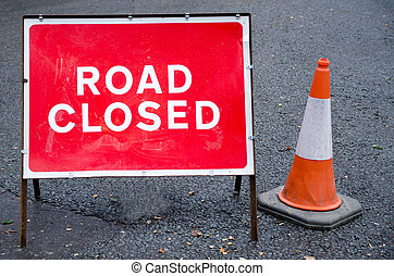 Road closed sign with traffic cone