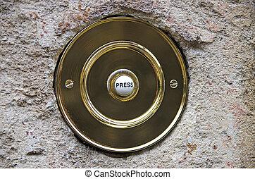 Brass doorbell - Circular brass doorbell on a stone wall