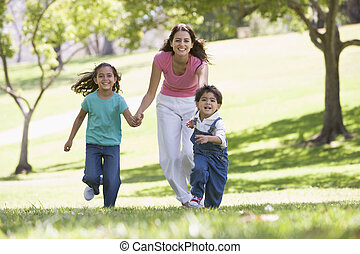 Woman with two young children running outdoors smiling