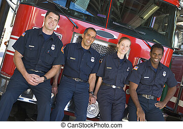 Four firefighters leaning on fire engine
