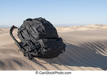 Backpack in desert - Loaded black military backpack sits on...
