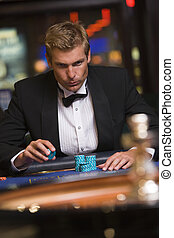 Man in casino playing roulette (selective focus)