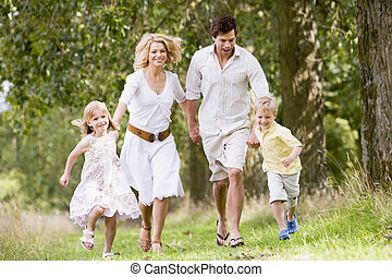 Family running on path holding hands smiling