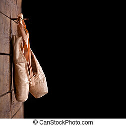 Used ballet shoes hanging on wooden background - Old used...