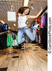 Beautiful happy brunette girl with shopping bag jumping in a...