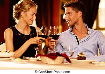 Beautiful young couple with glasses of red wine in luxury...