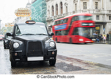 Taxi in London and red bus on the background