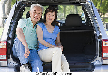 Couple sitting in back of van smiling