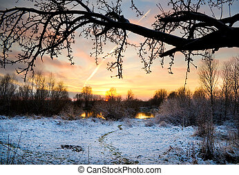 Winter landscape with sun and frozen river. Sunset.