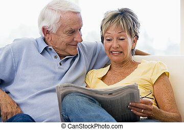 Couple in living room reading newspaper smiling