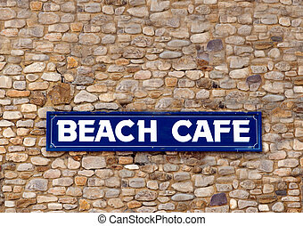 Beach cafe sign on stone wall