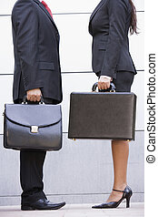 Two businesspeople standing outdoors holding briefcases