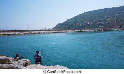 Two senior men fishing on sea shore, Alanya, Turkey -...