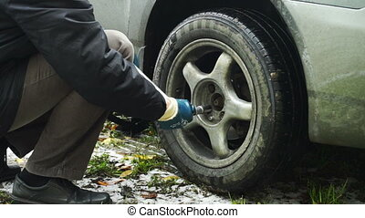 Man turning off screws from car rear wheel - Changing a car...