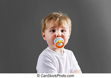 Baby boy with soother - Cute little blond baby boy or...