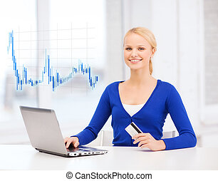 smiling woman with laptop computer and credit card - money,...