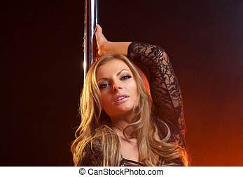 Portrait of a sensual female with blond hair with dance pole...