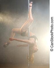 Young elegant female pole dancer posing upside down -...