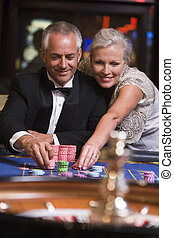 Couple in casino playing roulette and smiling (selective...