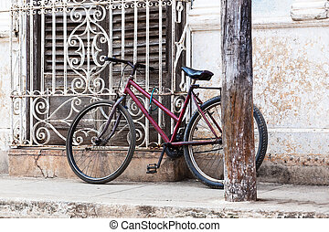 old red bicycle on city street