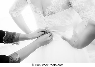Bride getting dressed and buttoned
