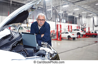 Mature auto mechanic. - Mature auto mechanic working in car...