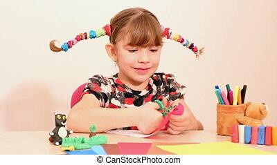 little girl makes paper mustache
