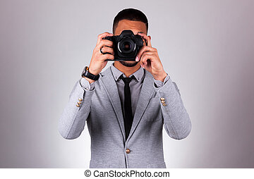African american photographer holding a dslr camera, over...