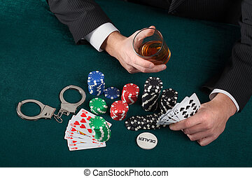 Gambler with alcohol and handcuffs - Gambler holding a glass...
