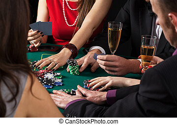 Poker game in progress, people sitting at casino table