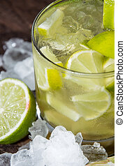 Glass of Caipirinha with Crushed Ice on wooden background