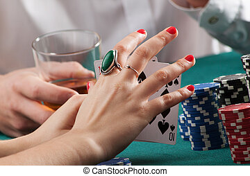Woman hands holding playing cards - Woman hands on green...