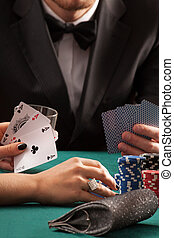 Poker game in casino, couple with cards