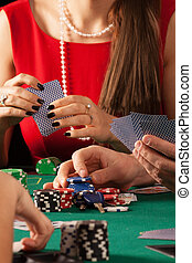 Gamblers playing poker game with cards and chips