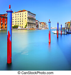 Poles and soft water on Venice lagoon in Grand Canal. Long exposure.