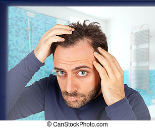 Man controls hair loss - Caucasian young man controls hair...