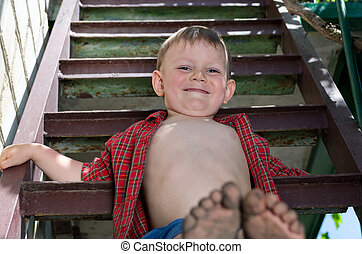 Little boy showing off his dirty feet sitting on a step...