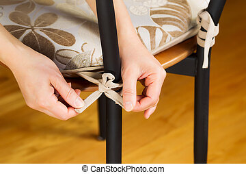 Putting seat cushion on chair - Horizontal photo of female...