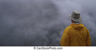 Uncertainty - A man in a yellow jacket gazes into the...