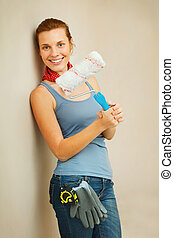 Happy woman with roller brush standing against wall.