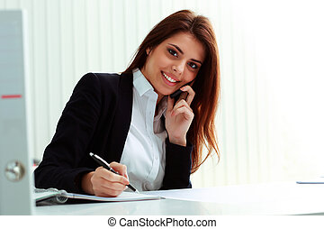 Young happy businesswoman talking on the phone and writing...