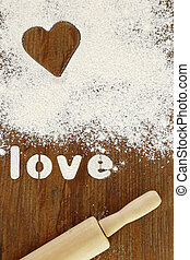 """Stencil word """"love"""" made with flour on wooden table"""