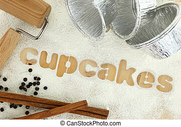 Stencil word quot;cupcakesquot; made with flour on wooden...