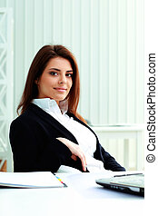 Young smiling businesswoman sitting at the table in office