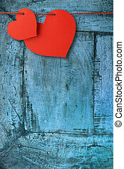 two heart-shaped cards hanging  on a blue plank
