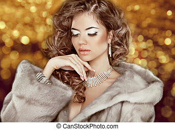 Luxury fashion beauty woman in fur coat over golden bokeh...