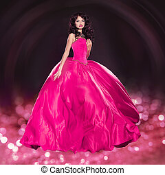 Beautiful woman in gorgeous dress over glitter gift...