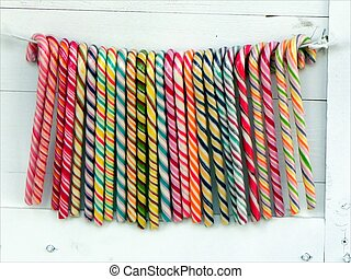 Lolly pops - Colorful sweets hanged on th wire on the white...