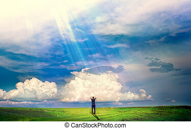 young boy stands in a field and the sun is shining on it