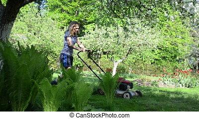 woman work garden lawn - woman model push lawn cutter...